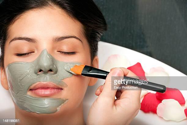 Woman having skin mask applied in bath