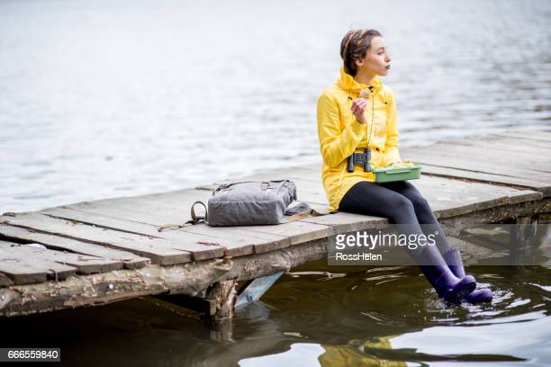 Woman having snack with lunch box on the pier