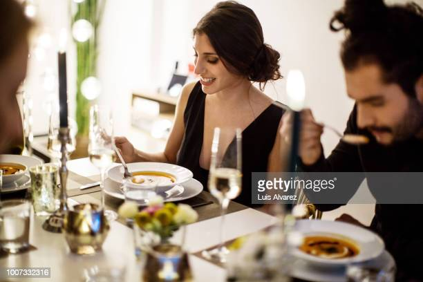 woman having squash soup at dining table - mensch im hintergrund stock-fotos und bilder