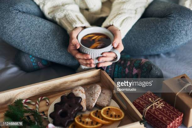 Woman having warm drink in front of tray of Christmas biscuits and gifts