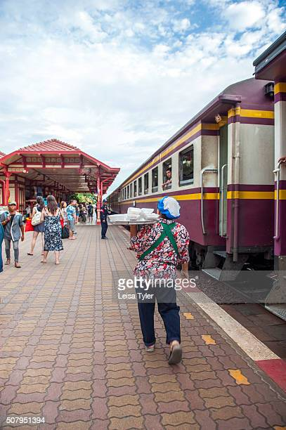 Woman hawking take away dishes to people on the train at the historical railway station in Hua Hin, Thailand.
