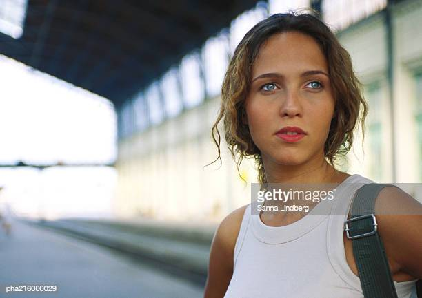 woman, head and shoulders, looking out of frame, train station in background - out of frame stock pictures, royalty-free photos & images