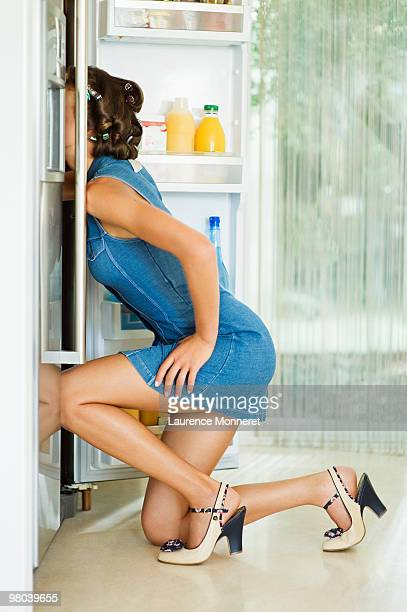 Woman head into her fridge sarching for food