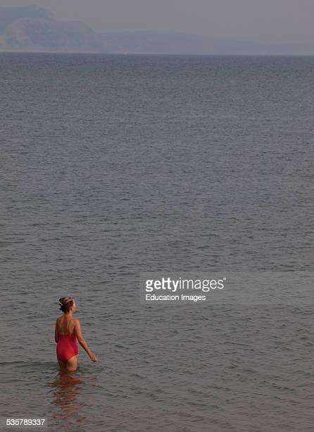 Woman heading into the sea for a swim, Lyme Regis, Dorset, UK.