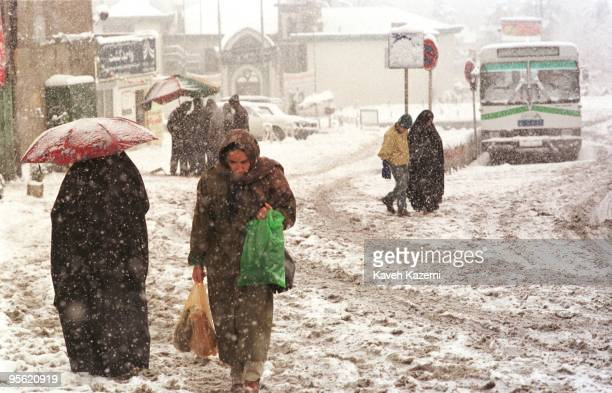 Woman heads home with her shopping through Tajrish Square in northern Tehran, during a heavy snowfall, 1996.