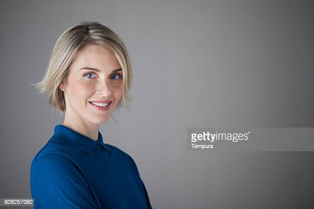 woman headshot looking at camera. - gray background stock pictures, royalty-free photos & images