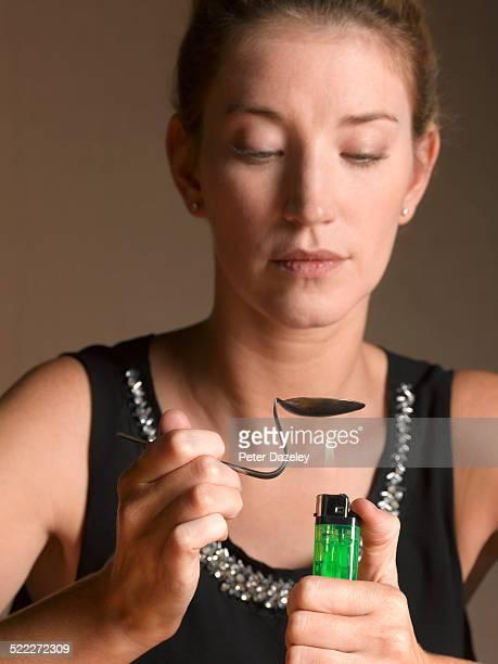 Woman heating spoon/heroin