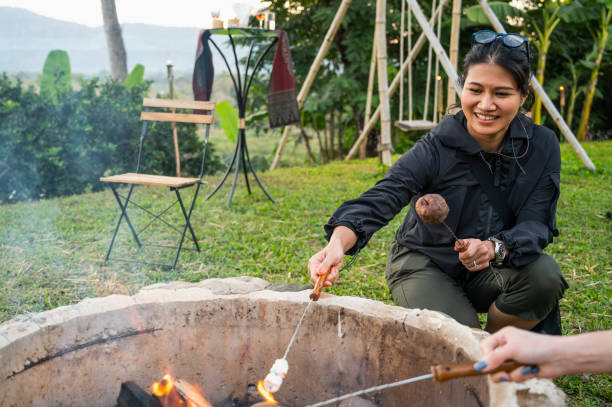 woman heating up marshmallows over camp fire in the Golden Triangle