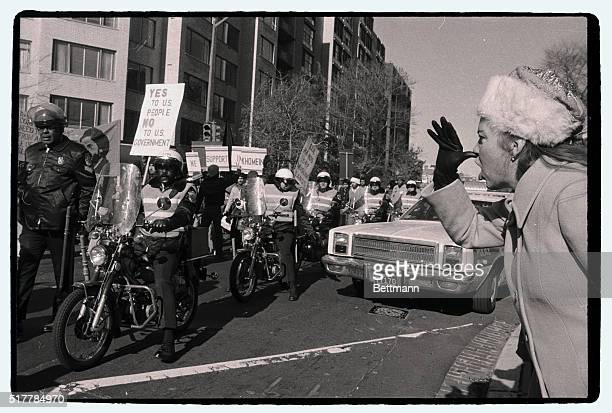 A woman heckler thumbs her nose at policeprotected Moslem student chanting 'long live Khomeini' as they parade to the State Department 11/30 to...