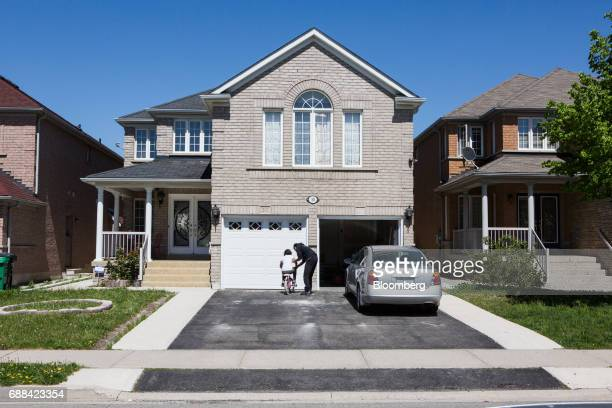 A woman helpd a girl ride a bike in front of a house in Brampton Ontario Canada on Saturday May 20 2017 After a double whammy of government...