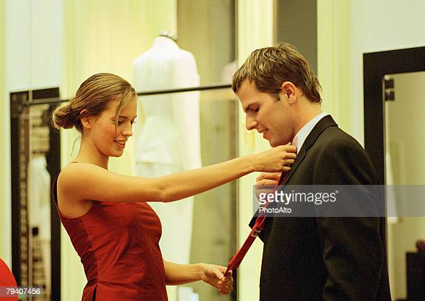 A woman helping a man pick out a tie