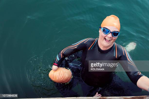 woman helping amputee friend out of the water - doing a favor stock pictures, royalty-free photos & images