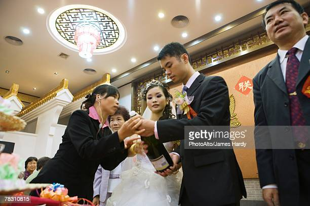 Woman helping bride and groom open champagne bottle, low angle view