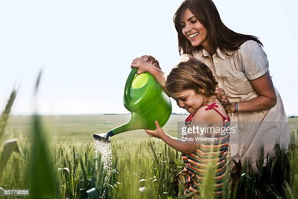 Woman helping child with watering can