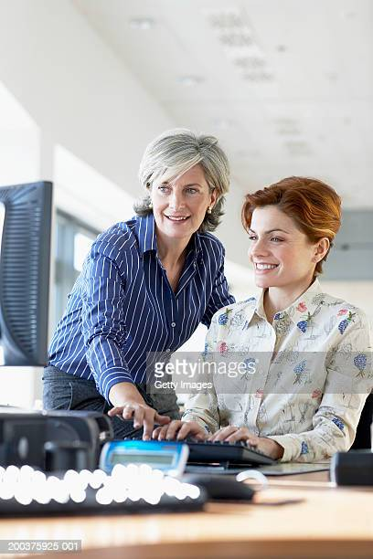 woman helping colleague at desk in office, smiling - blue blouse stock pictures, royalty-free photos & images