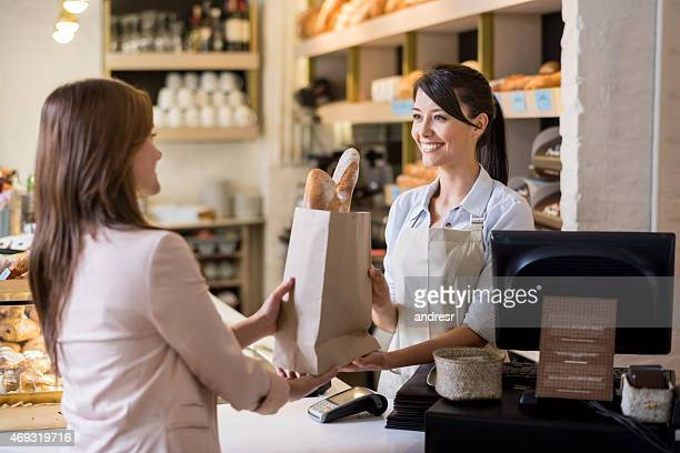 woman helping customer at the bakery - happy merchant stock pictures, royalty-free photos & images