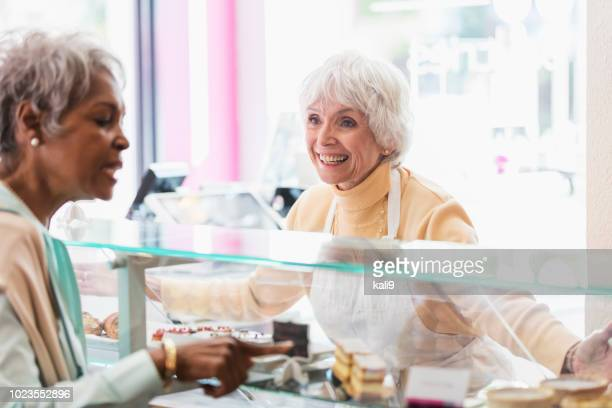woman helping customer in pastry shop - franchising stock pictures, royalty-free photos & images