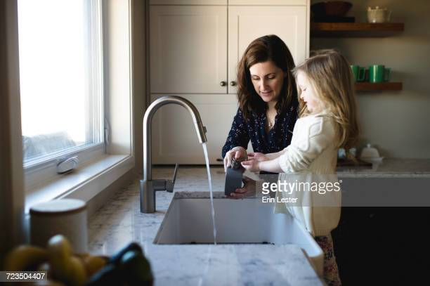 Woman helping daughter wash hands at kitchen sink