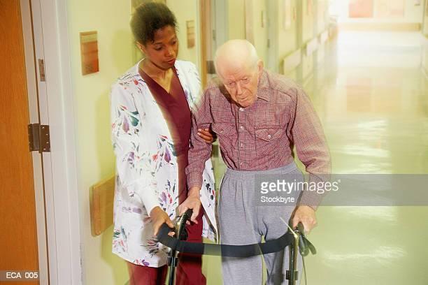 Woman helping elderly man walk down hallway using walking frame