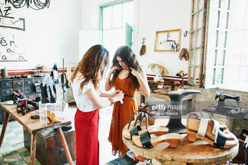 Woman helping friend try on handmade leather belt while shopping together in boutique : Stock Photo