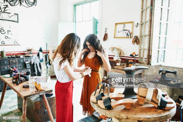 woman helping friend try on handmade leather belt while shopping together in boutique - leather belt stock pictures, royalty-free photos & images