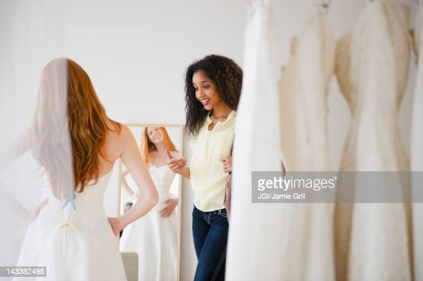 Woman helping friend try on wedding dress