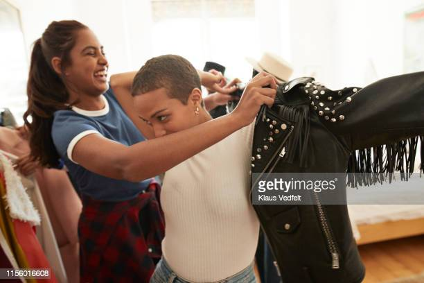 woman helping friend wearing black leather jacket - black jacket stock pictures, royalty-free photos & images