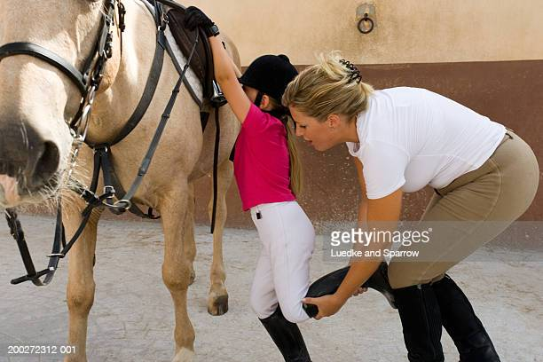 Woman helping girl (4-6) onto horse