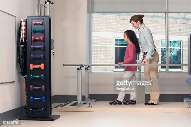 Mulher ajuda a menina Passeio no Centro de reabilitação