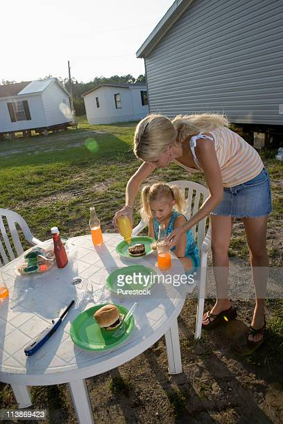 Woman helping girl with her food at a picnic table outside trailer homes