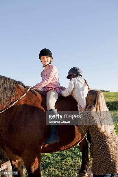 Woman helping girls on horseback