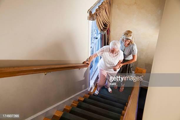 Woman helping grandmother climb stairs