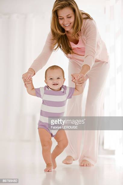 Woman helping her daughter to walk