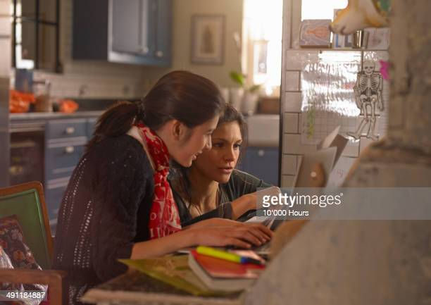 Woman helping her daughter with her homework