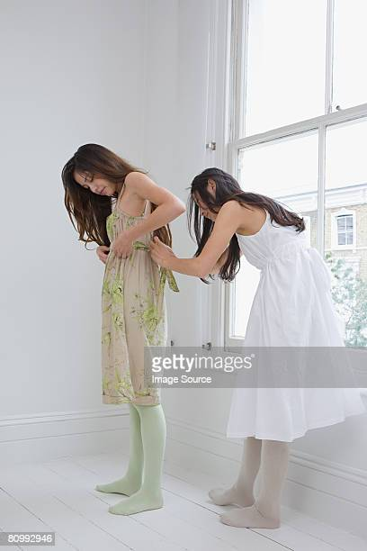 a woman helping her friend tie a belt - mongolian women stock photos and pictures