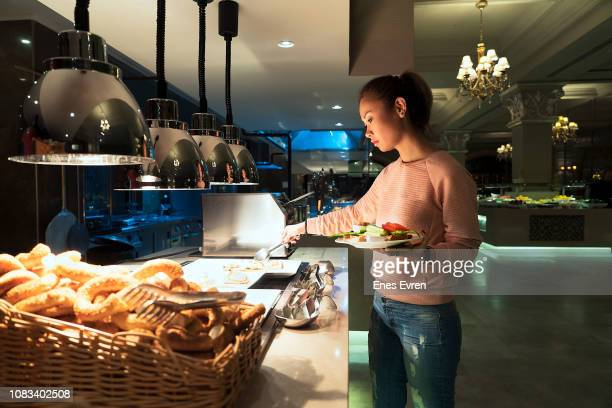 woman helping herself to the breakfast buffet in a luxury hotel's restaurant - buffet stock pictures, royalty-free photos & images