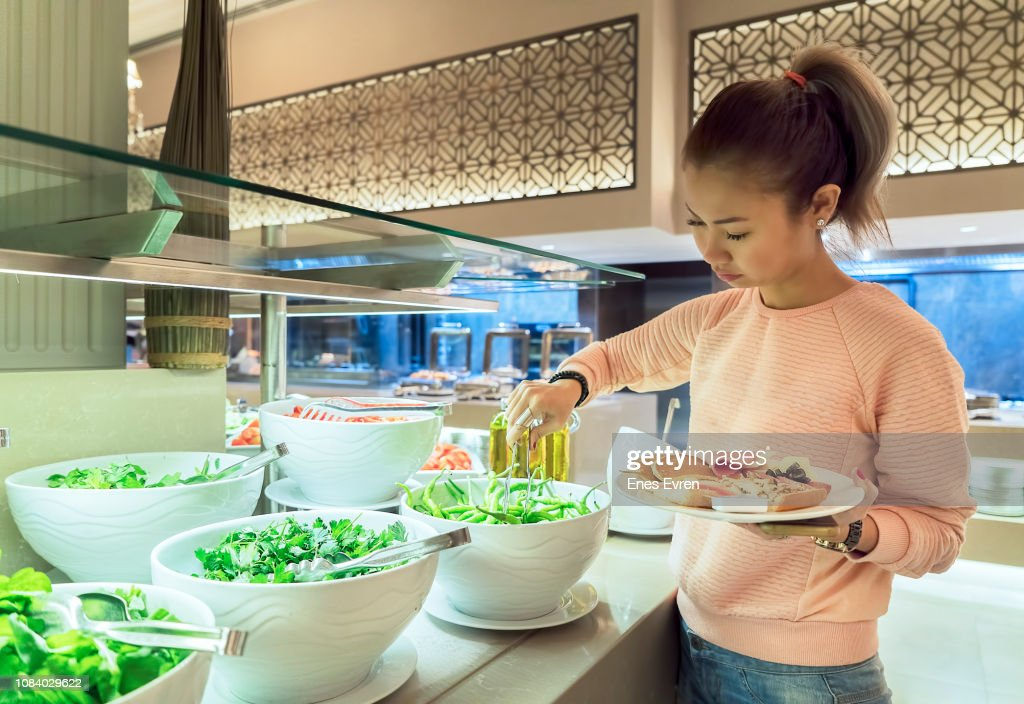 Woman helping herself to the breakfast buffet in a luxury hotel's restaurant : Stock Photo