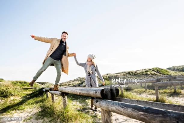 Woman helping man balancing on wooden stakes in dunes