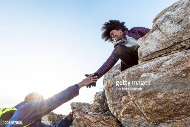 woman helping man up rock outcrop, kittery, maine, usa - a helping hand stock pictures, royalty-free photos & images