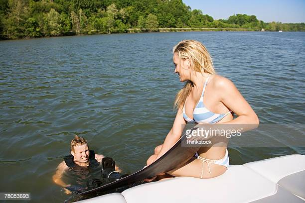 Woman helping man with wakeboard onto boat