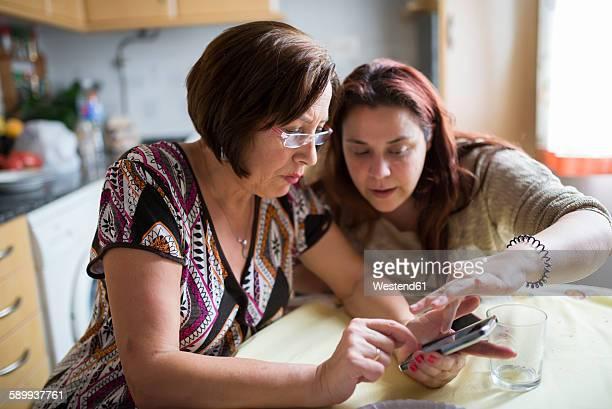 woman helping senior woman how to use a smartphone - profesora mayor fotografías e imágenes de stock