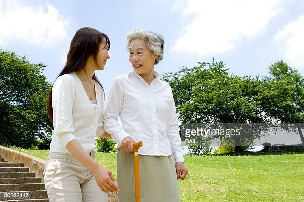 Woman helping senior woman walking down stairs, smiling