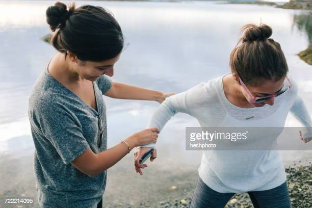woman helping sister on shingle beach, maine, usa - heshphoto stockfoto's en -beelden