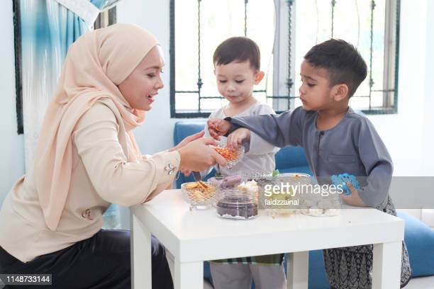 a woman helping to serve raya cookies on eid-ul-fitr / aidilfitri - malaysian culture stock pictures, royalty-free photos & images