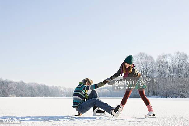 woman helping up fallen man - ice skating stock pictures, royalty-free photos & images