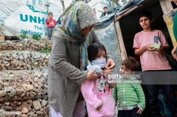 TOPSHOT A woman helps a child with a mask after members of NGO Team Humanity gave out handmade protective face masks to migrants and refugees in the...
