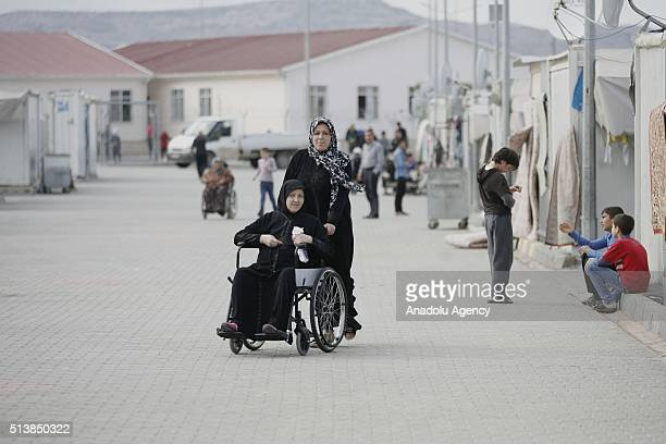 A woman helps a disabled Syrian woman in a wheelchair at the container city housing 1340 women and more than two thousands children who fled war in...