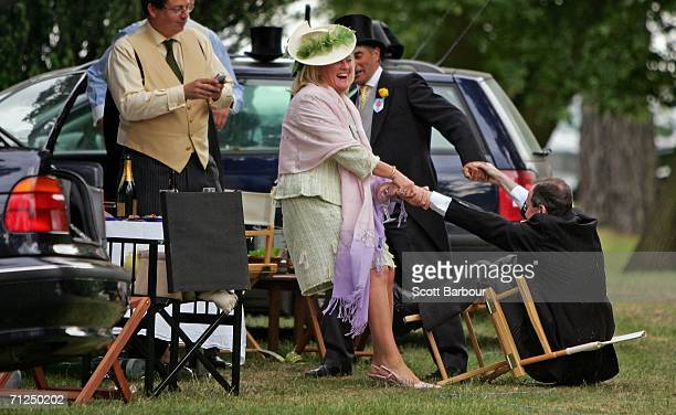 A woman helps a man after he fell from his chair as racegoers have a party in the car park after attending the first day of Royal Ascot at the Ascot...