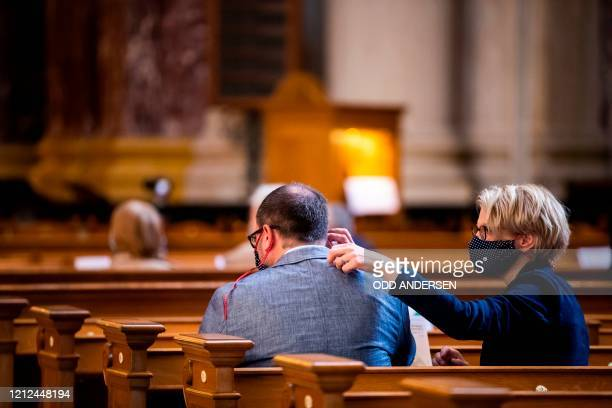 Woman helps a man to fit a protective face mask as members of the congregation observe social during a Sunday service at the Berliner Dom cathedral...