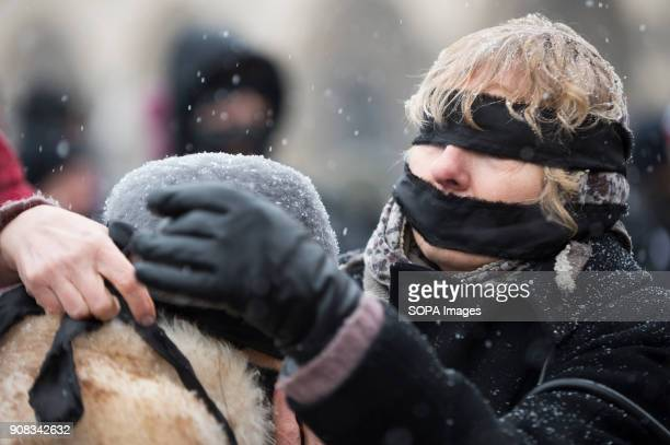 A woman helps a protestor to put black bands over her eyes and mouth during a silent assembly named Stolen Justice in Krakow Stolen Justice happening...